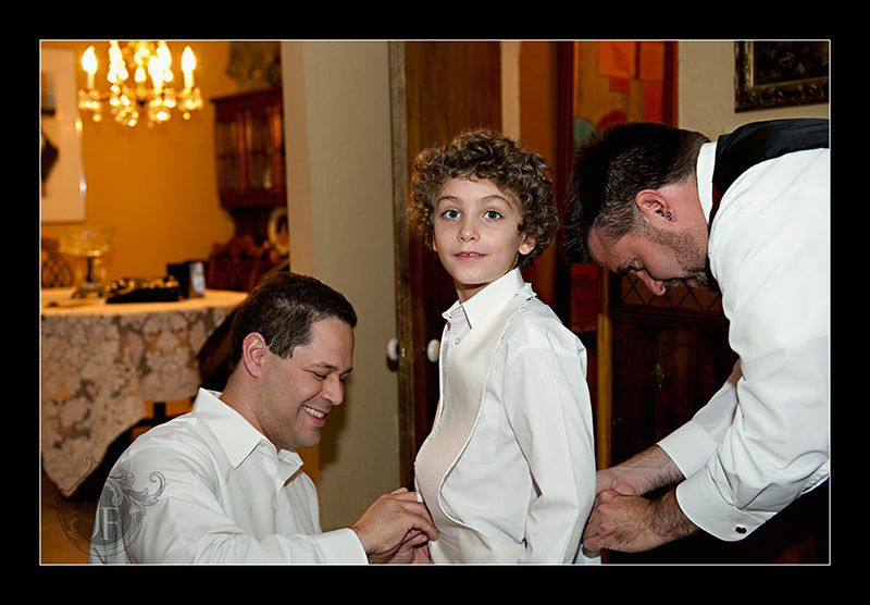 Ross and fellow groomsman John help young ring bearer Joshua, Mary's son, get into his clothes. (Steve Glass - Nikon D700)